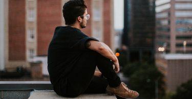 man-zittend-zwarte-kleding